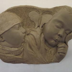 Relief in bruin gebakken klei van twee babi's, links heel jong rechts een paar weken oud slapend en een vlinder, op RVS plaat