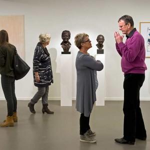 6 mensen kijken verschillende kanten op bij het bekijken van een expositie