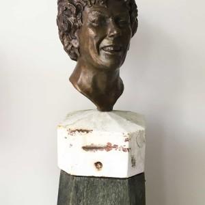 Lachend portret van een vrouw met krullen in brons op een meerpaal