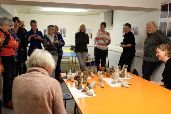Groep mensen tevreden kijkend naar een tafel met net geboetseerde beeldjes tijdens bespreking