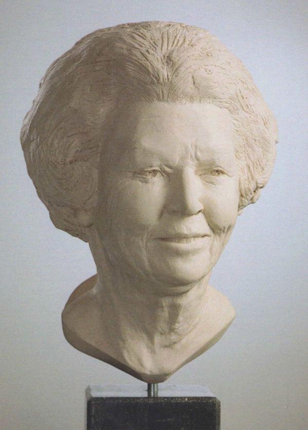Gedetailleerd licht glimlachend portret van prinses Beatrix  in zandkleurig gebakken klei