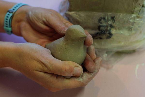Close-up van twee handen die een vogeltje boetseren van klei, alsof er een vogeltje in de handen zit