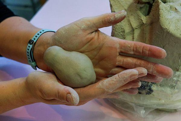 Close-up van twee handen die een vogeltje boetseren van klei, als een ei ligt het in de handen