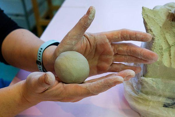 Close-up van twee handen die een vogeltje boetseren van klei, als een balletje in de handen