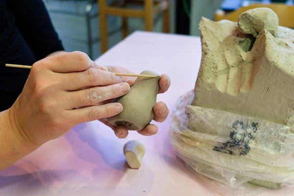 Close-up van twee handen die met een satéprikker een detail tekenen in een vogeltje dat geboetseerd is van klei, het vogeltje in de handen houdend