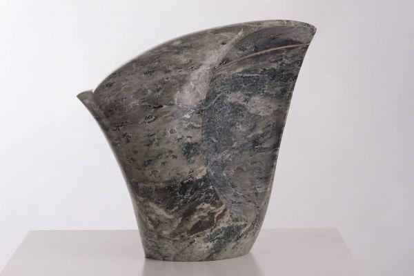 Beeld van grijs groen gemêleerd marmer, onderkant smal naar boven uitlopend, rechterhelft is een holle vorm met een goudkleurige lijn van brons