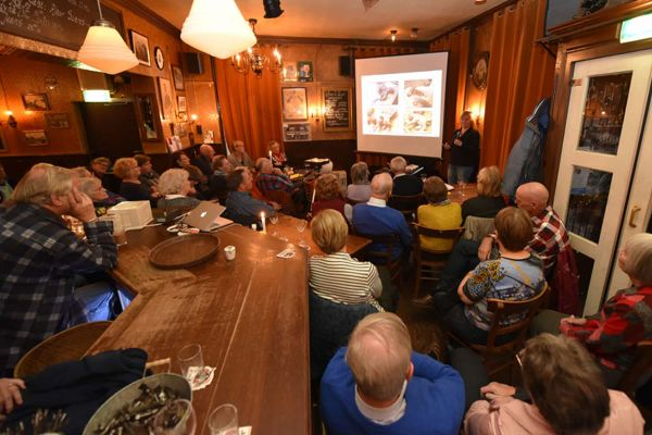 Groep volwassenen aangeschoven tussen tafeltjes en de bar kijkend naar een scherm en Myrte in de hoek van een bruin cafe