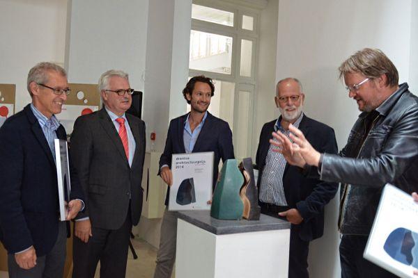 5 mensen (de eerste winnaars) om de beelden van de architectuurprijs heen