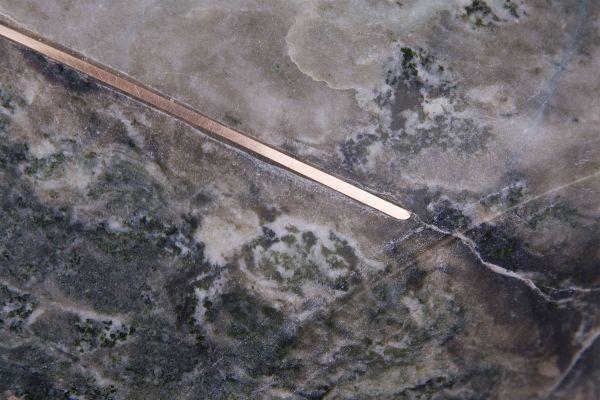 Detail van grijs groen gemêleerd marmer met een goudkleurige lijn van brons