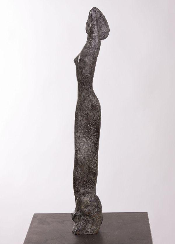 Lang bronzen beeld, van uitrekkende jonge vrouw met jong poesje bij haar voet