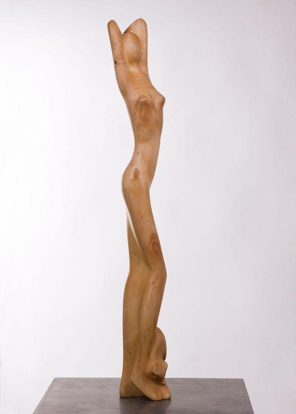 Lang houten beeld, van uitrekkende jonge vrouw met jong poesje bij haar voet