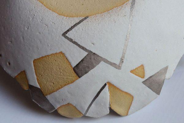 Detail zijkant ronde schaal keramiek wit, met hoekige vormen in zandkleur en zilver