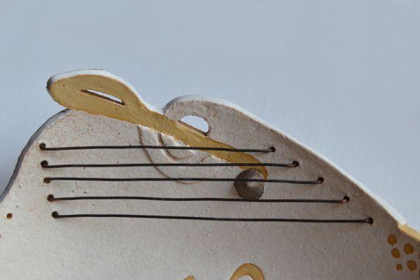 Detail ronde schaal keramiek wit en zandkleur, vioolsleutel koperen draden als snaren