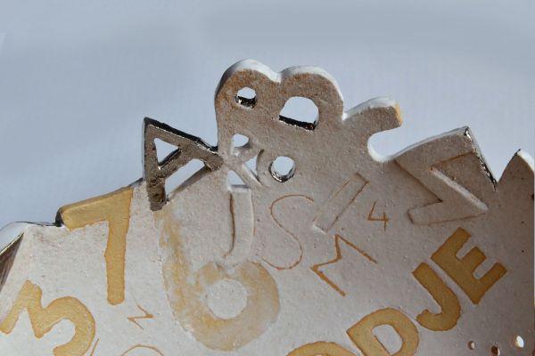 Detail ronde schaal keramiek, wit met tekst en cijfers en letters in zandkleur en zilver