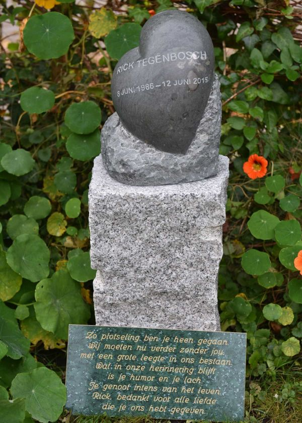 Beeld van dolomiet steen op grove wit granieten sokkel, hartvorm met naam en geboorte- en sterfdatum erin gegraveerd