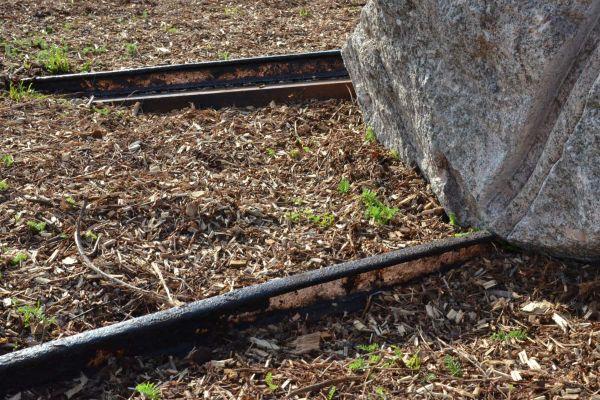 Detail bruin treinspoor uit de grond naar zwerfkei met spoor erin uitgehakt