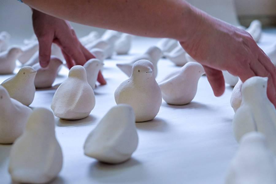 Close-up van een groep crèmekleurige gestileerde vogeltjes van keramiek en twee handen die de vogeltjes neerzetten op witte achtergrond