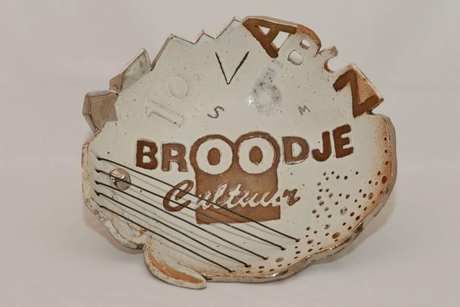 Keramiek ronde schaal wit met bruin en zilver met tekst en cijfers en letters, koperen draden als snaren, gaatjes en vormen aan de rand